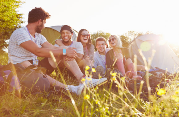 Group Of Friends Relaxing Outside Tents On Camping Holiday