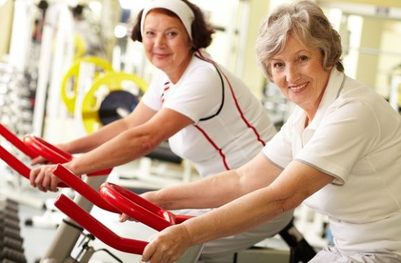 Photo of two smiling middle-aged women on exercise bikes